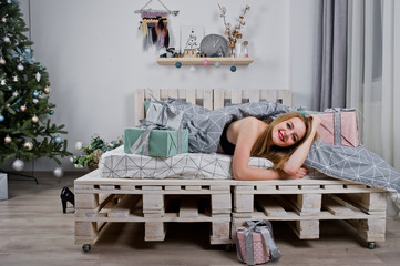 Cute blonde girl on black bra lying on bed with gifts boxes against new year tree at studio. Happy holidays.