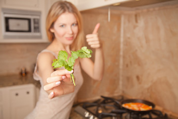 a beautiful woman stands and holds parsley, fry eggs