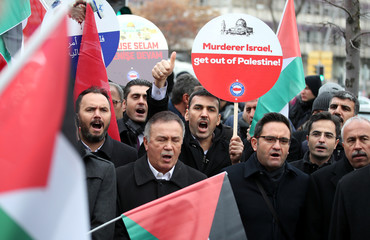 Demonstrators hold Turkish and Palestinian flags as they shout slogans during a protest against U.S. near the U.S. Embassy in Ankara