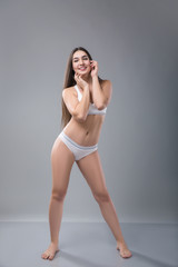 Beautiful plump woman or plus size model in the sports underwear on a grey background