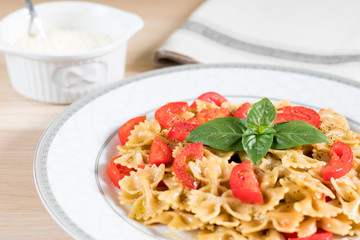 Italian pasta farfalle with pesto sauce, tomato, basil and pepper. Bowl with grated parmesan cheese and kitchen towel. Wooden surface background.