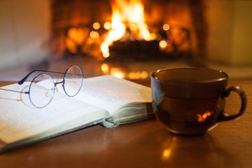 An open ancient book, antique glasses and a cup of hot drink in front of the fireplace. Evening fairy tales. Fantasy.