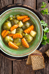 Vegetable soup with brussel sprouts on wooden rustic table, top view