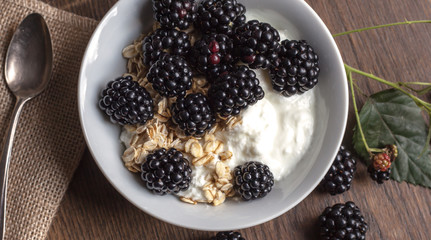 Fresh blackberries ant oatmeal snack on rustic table Background