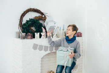 The guy schoolboy sits at the fireplace and holds the box with a gift in his hands