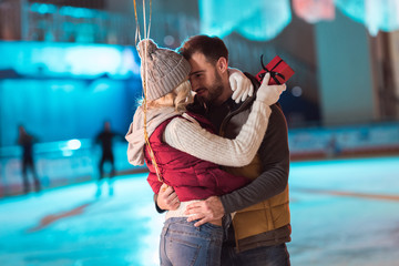 happy young couple hugging on rink while girl holding gift box