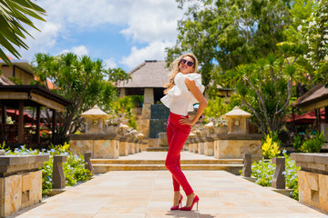 Fashionable woman in red leather pants and high heels