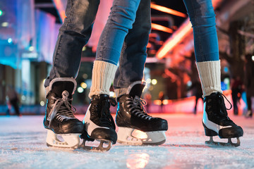 close-up partial view of young couple in skates ice skating on rink
