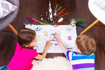 Young children girl and boy painting astronaut costume by pens and dreaming about cosmos with cosmonaut constructor toys: rocket, shuttle and rover in comfortable interior at home on wooden floor