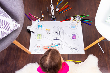 Young child girl female painting astronaut costume by colorful pens and dreaming about cosmos with cosmonaut constructor toys: rocket, shuttle and rover in comfortable interior at home on wooden floor
