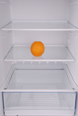 One orange in open empty refrigerator.