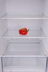 One pepper in open empty refrigerator.