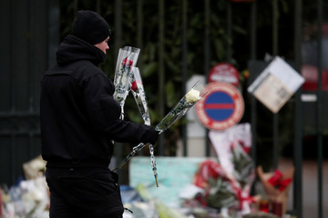 A security agent places flowers brought by fans of late French singer and actor Johnny Hallyday outside his home in Marnes-la-Coquette near Paris