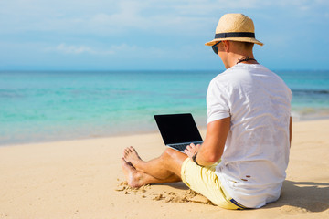 Casual looking guy using laptop on the beach