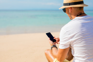 Guy using phone on the beach