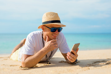 Man using mobile phone on the beach