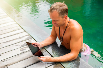 Man looking at tablet while resting in the pool
