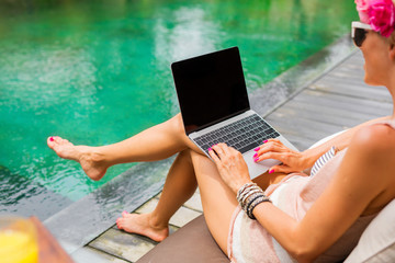 Hipster woman using laptop by the pool