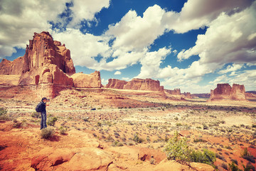 Female photographer takes pictures in Arches National Park, color toned image, Utah, USA.