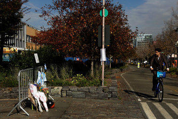 A bicyclist passes a memorial on West Street two days after a man driving a rented pickup truck mowed down pedestrians and cyclists on a bike path alongside the Hudson River, in New York
