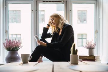 Dreaming woman enjoying book at home