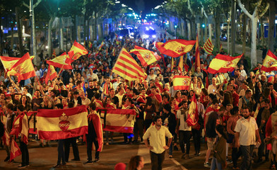 Pro unity demonstrators wave Spanish and Catalan flags during a protest after the Catalan regional parliament declared independence from Spain in Barcelona
