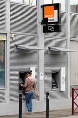 A woman withdraws money from an Orange Bank cash machine outside the Bank headquarters in Montreuil near Paris