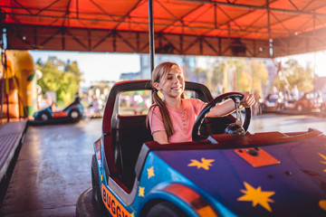 Girl driving electric cars in amusement park