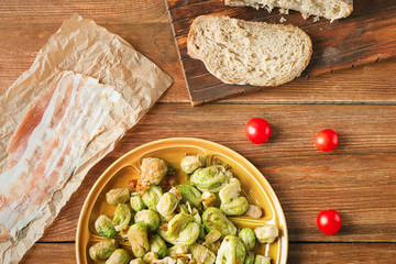 Plate with roasted Brussel sprouts and bacon on wooden table