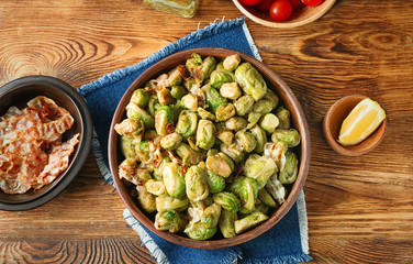 Bowl with roasted Brussel sprouts and bacon on wooden table