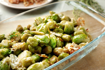 Baking dish with roasted Brussel sprouts and bacon on table, closeup