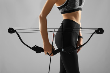 Sporty young woman with bow and arrow for practicing archery on grey background