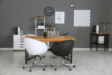 Modern office interior with black and white armchairs