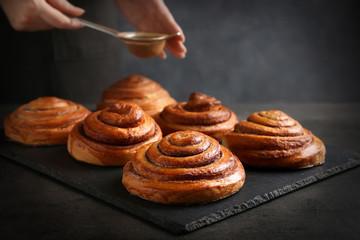 Woman sprinkling sweet rolls with cinnamon on slate plate