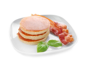 Tasty breakfast with pancakes and bacon on white background