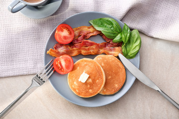 Tasty breakfast with pancakes, bacon and tomato on plate