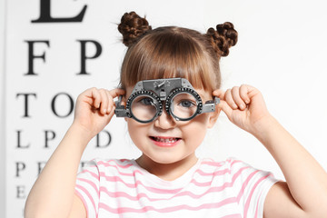Cute little girl with trial frame in ophthalmologist's office