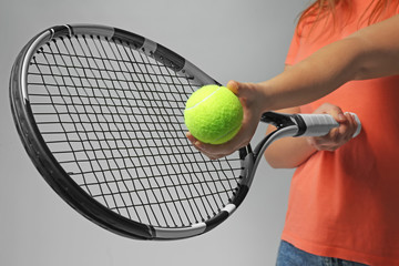 Woman with tennis racket and ball on light grey background