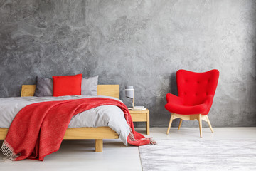 Red armchair next to bed