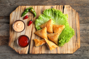 Wooden board with delicious meat samosas on table