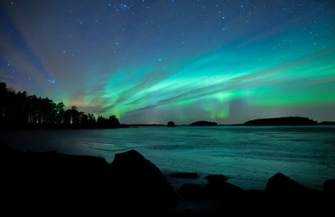 Northern lights dancing over frozen lake in Farnebofjarden national park in Sweden.