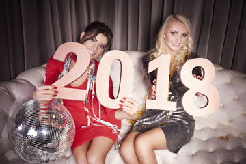Women with new year's number sitting on sofa at night club. Focus on digits