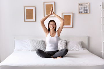 Young woman practicing yoga in bed at home