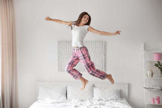 Young woman jumping on bed at home