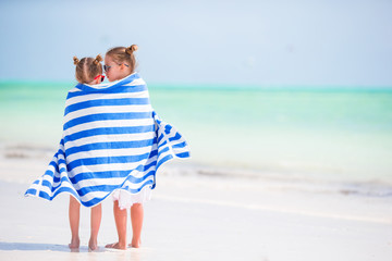 Little cute girls wrapped in towel at tropical beach. Kids on the beach vacation