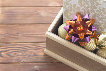 An edge of a wooden box filled with shiny golden balls and a light patterned gift box with a burgundy bow. Rustic wooden background.