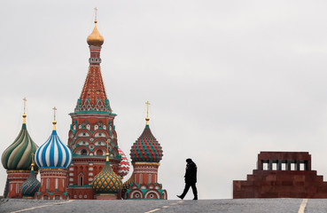 Police officer walks along the Red Square with St. Basil's Cathedral and Lenin Mausoleum seen in the background, in Moscow