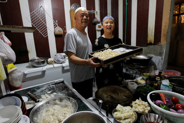 Halima and her husband Saleh pose for a picture in the kitchen of the Chinese Muslim restaurant in Islamabad