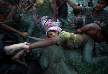 Photographers help a Rohingya refugee to come out of Naf River as they cross the Myanmar-Bangladesh border in Palong Khali, near Cox's Bazar