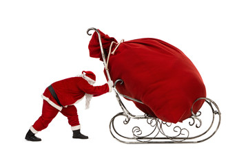 Santa Claus pushing sleigh with huge bag full of christmas gifts isolated on white background